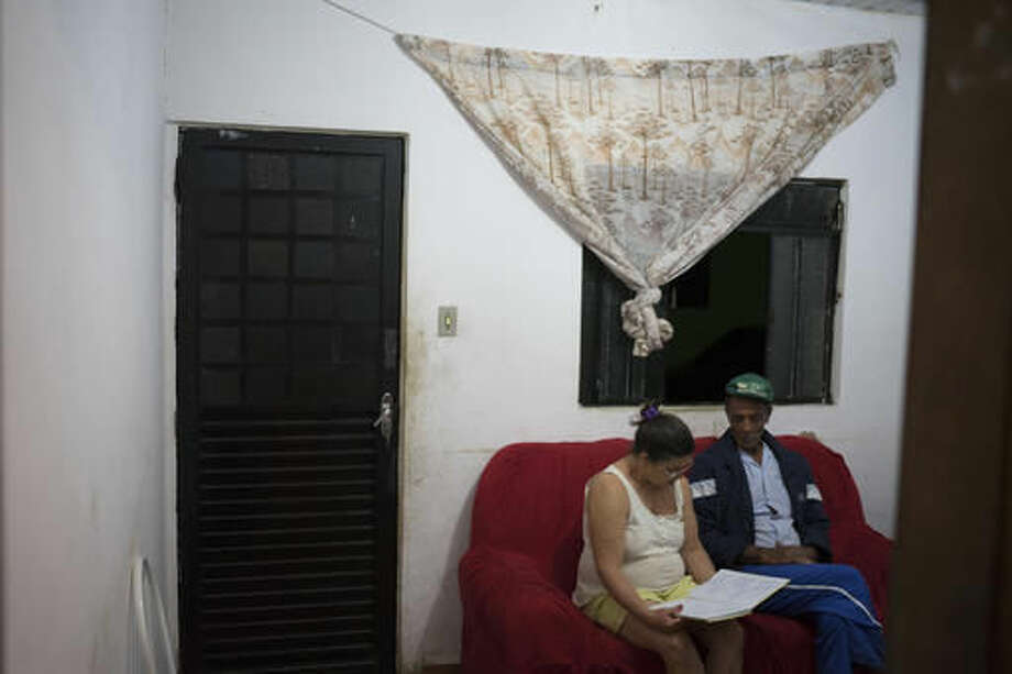 """In this Oct. 13, 2016 photo, Maria do Carmo Pereira Ramos, left, sits next to her husband Jose do Patrocinio de Oliveira, in Mariana, Brazil, as she reads aloud a poem she wrote about the tragedy of their hometown. She wrote, """"With sadness in our heart we left our place, where we raised our sons, and the homesickness will stay. Paracatu and Bento Rodrigues in the history will stay, we may go back one day, but it never again will be the same."""" (AP Photo/Leo Correa)"""