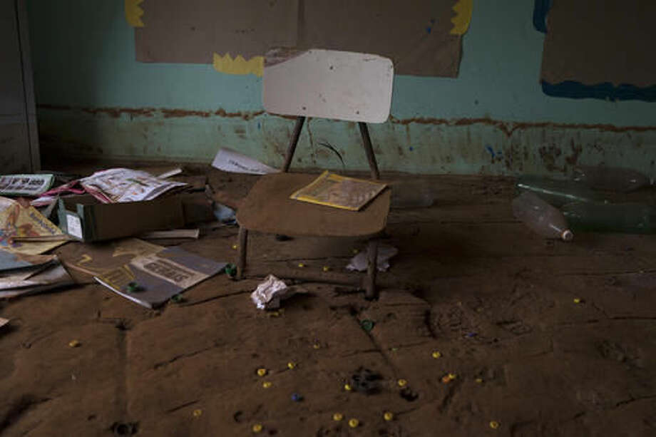 In this Oct. 13, 2016 photo, a chair is embedded in dried mud in the classroom of a school destroyed by a mudslide triggered by the Nov. 5, 2015 failing of a dam holding back a giant pond of mine waste, in Paracatu, Brazil. Families whose lives were upended by the tragedy, say they feel betrayed by the company behind it, Samarco, which is a joint venture of two of the world's mining giants, Vale of Brazil and BHP Billiton of Australia. (AP Photo/Leo Correa)
