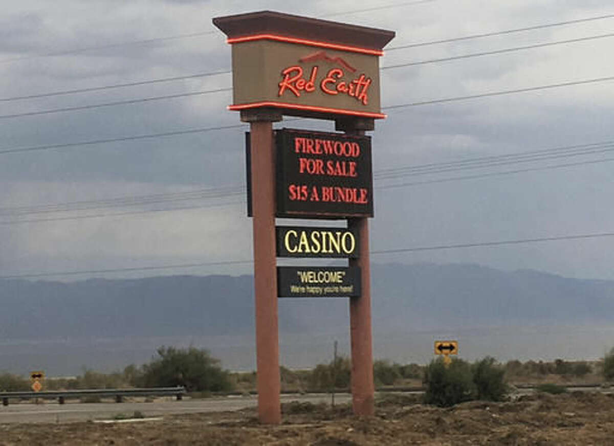 In this Monday, Oct. 24, 2016, photo, a sign with the Salton Sea in the background, marks the road to the Red Earth Casino in Thermal, Calif. Bus tours have been a fixture across the American landscape for years, shuttling gamblers from cities to rural places casinos are located, particularly in California where tribal operations are often hours away. A deadly California casino bus crash has focused federal regulators on the niche tour industry. (AP Photo/Elliot Spagat)