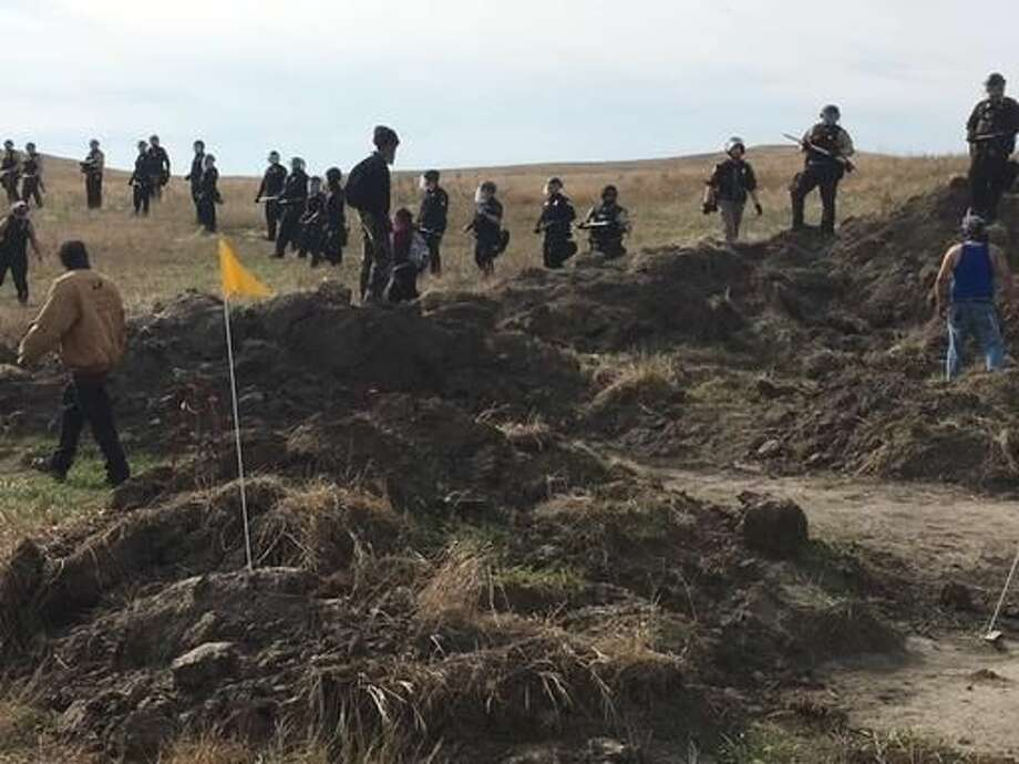 Demonstrators stand near armed soldiers and law enforcement officers who moved in to force Dakota Access pipeline protesters off private land in North Dakota on Thursday, Oct. 27, 2016 where they had camped to block construction. The pipeline is to carry oil from western North Dakota through South Dakota and Iowa to an existing pipeline in Patoka, Ill. (Mike McCleary/The Bismarck Tribune via AP)