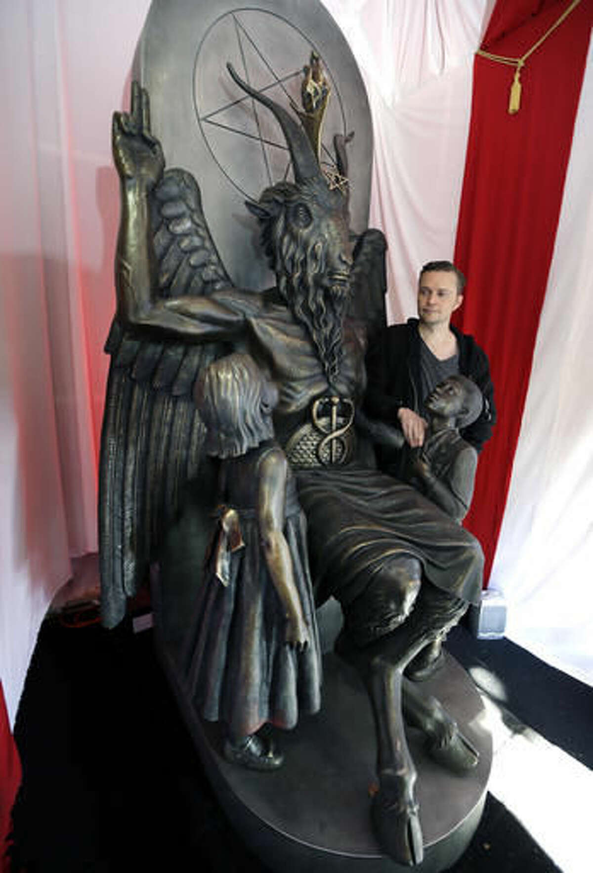 """In this Oct. 24, 2016 photo, Lucien Greaves stands next to a 9-foot statue of the goat-headed idol Baphomet at the recently opened international headquarters of the Satanic Temple in Salem, Mass. The Satanic Temple is waging religious battles along a variety of fronts nationwide, and its co-founder says it's just getting started. Greaves says the temple hopes to ensure Satanists """"have a place in the world"""" and that """"evangelical theocrats"""" don't monopolize the religious freedom debate. (AP Photo/Elise Amendola)"""