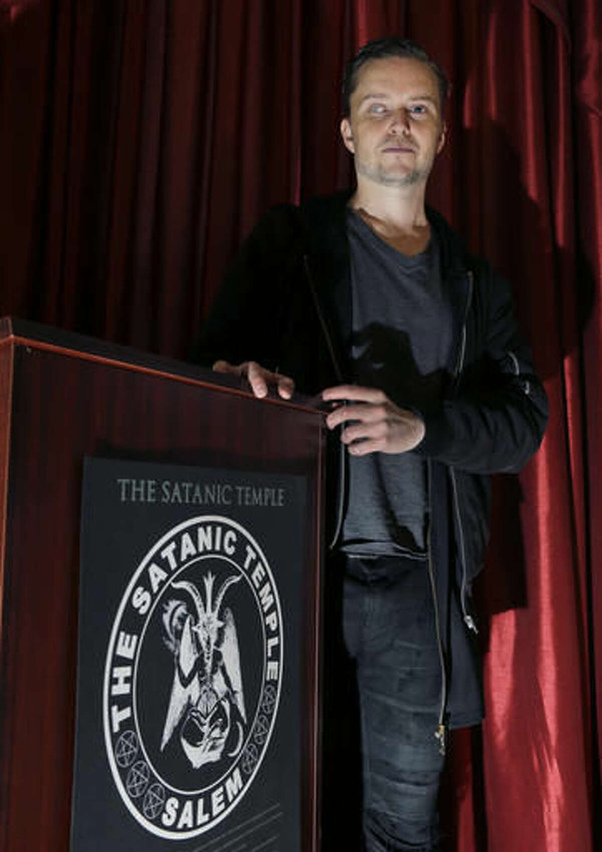 """In this Oct. 24, 2016 photo, Lucien Greaves stands inside the recently opened international headquarters of the Satanic Temple in Salem, Mass. The Satanic Temple is waging religious battles along a variety of fronts nationwide, and its co-founder says it's just getting started. Greaves says the temple hopes to ensure Satanists """"have a place in the world"""" and that """"evangelical theocrats"""" don't monopolize the religious freedom debate. (AP Photo/Elise Amendola)"""