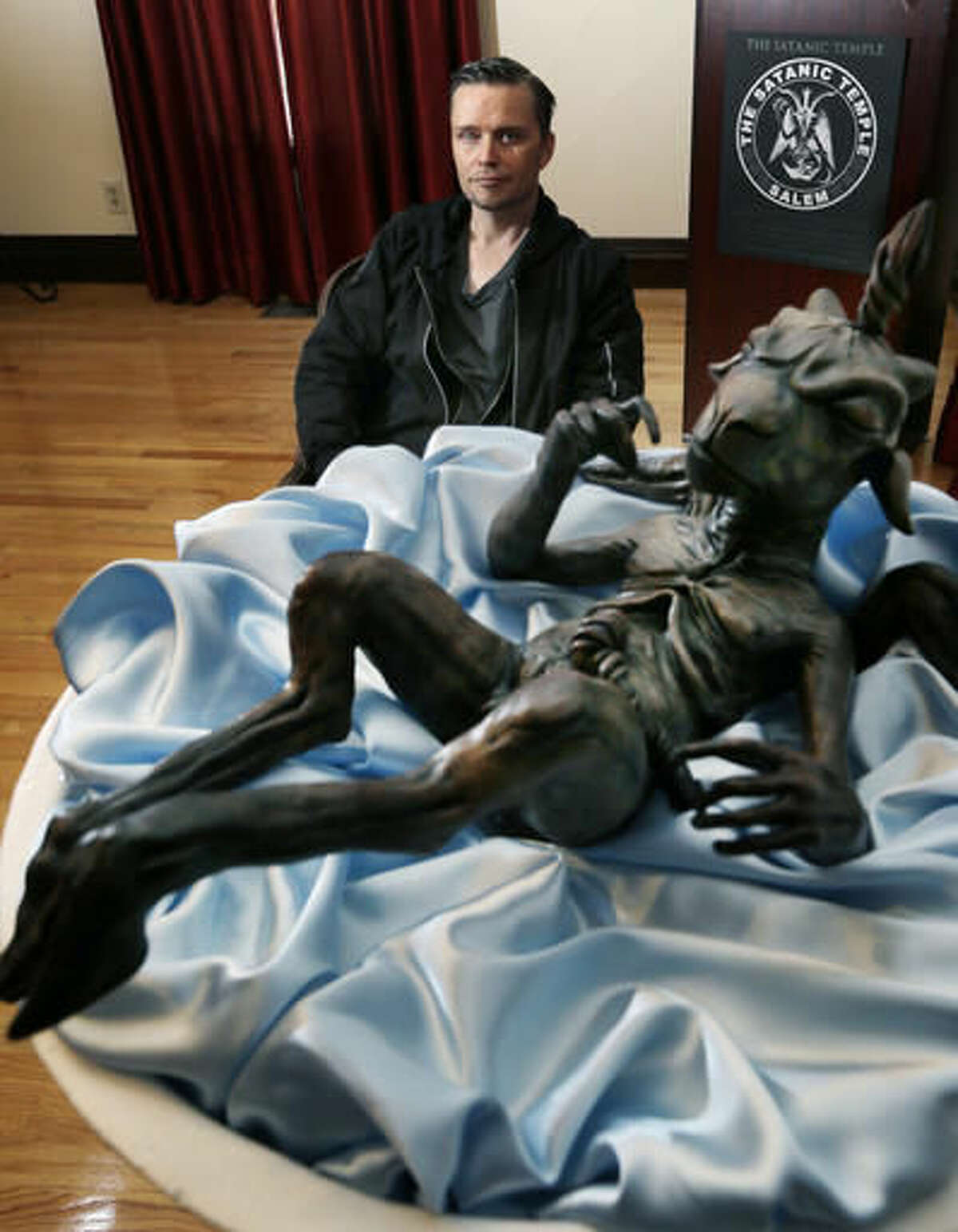 In this Oct. 24, 2016 photo, Lucien Greaves sits near a statue of a baby Baphomet inside the recently opened international headquarters of the Satanic Temple in Salem, Mass. The Satanic Temple is waging religious battles along a variety of fronts nationwide, and its co-founder says it's just getting started. Greaves says the temple hopes to ensure Satanists