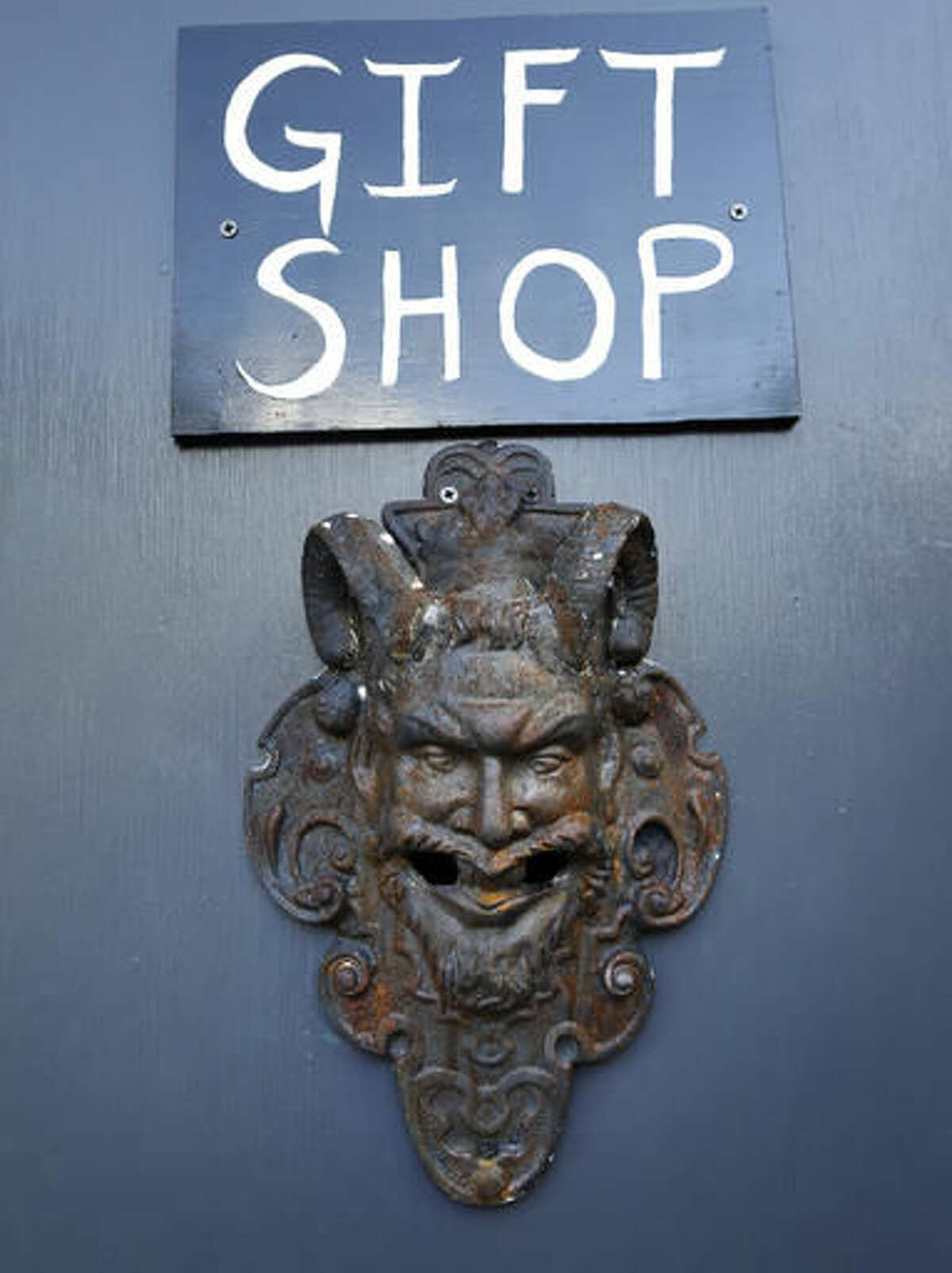 """In this Oct. 24, 2016 photo, the gift shop door is seen at the recently opened international headquarters of the Satanic Temple in Salem, Mass. The Satanic Temple is waging religious battles along a variety of fronts nationwide, and its co-founder Lucien Greaves says it's just getting started. Greaves says the temple hopes to ensure Satanists """"have a place in the world"""" and that """"evangelical theocrats"""" don't monopolize the religious freedom debate. (AP Photo/Elise Amendola)"""