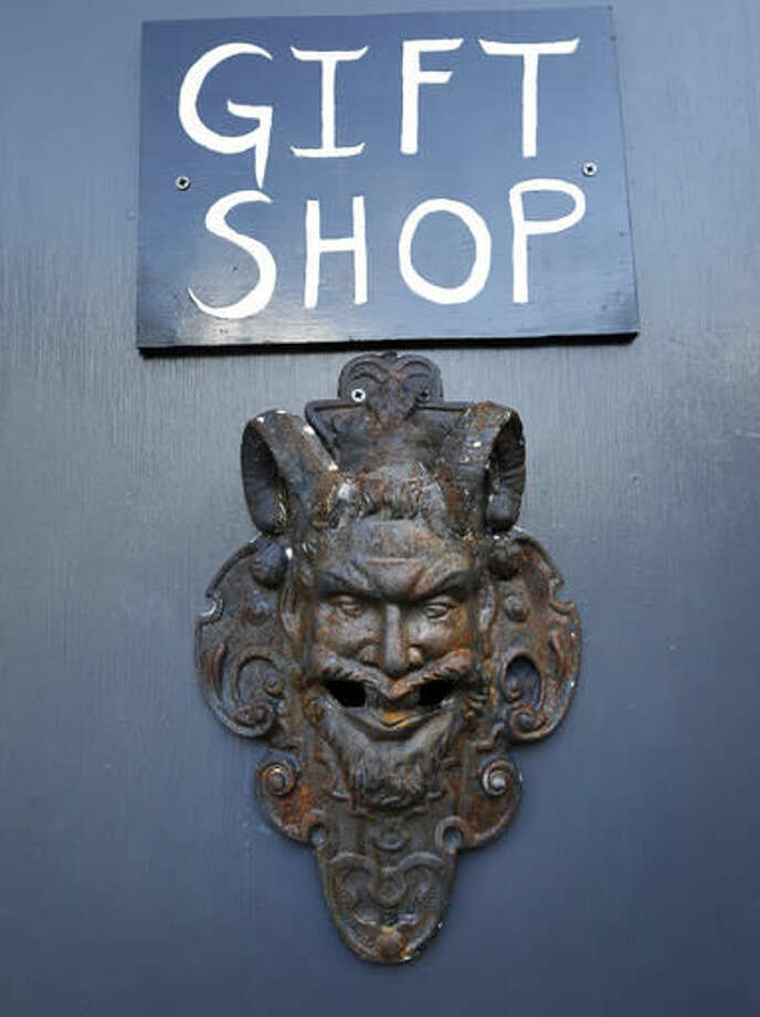 "In this Oct. 24, 2016 photo, the gift shop door is seen at the recently opened international headquarters of the Satanic Temple in Salem, Mass. The Satanic Temple is waging religious battles along a variety of fronts nationwide, and its co-founder Lucien Greaves says it's just getting started. Greaves says the temple hopes to ensure Satanists ""have a place in the world"" and that ""evangelical theocrats"" don't monopolize the religious freedom debate. (AP Photo/Elise Amendola)"