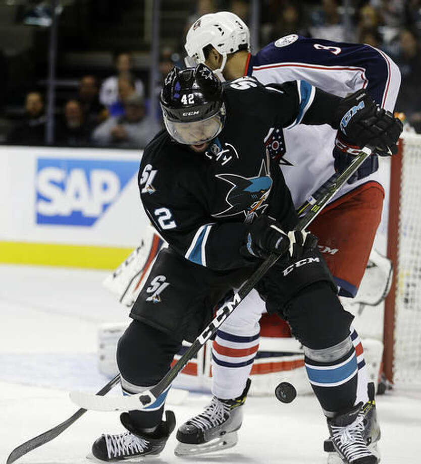 San Jose Sharks' Joel Ward (42) andColumbus Blue Jackets' Seth Jones (3) fight for the puck during the first period of an NHL hockey game Thursday, Oct. 27, 2016, in San Jose, Calif. (AP Photo/Ben Margot)