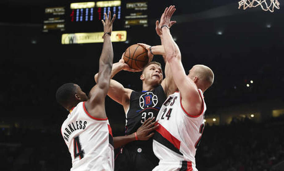 Los Angeles Clippers forward Blake Griffin drives to the basket against Portland Trail Blazers forward Maurice Harkless and forward Mason Plumlee during the first quarter of an NBA basketball game in Portland, Ore., Thursday, Oct. 27, 2016. (AP Photo/Steve Dykes)