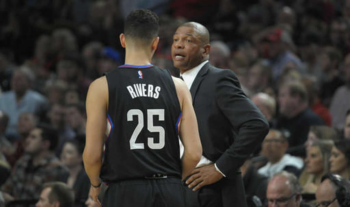 Los Angeles Clippers head coach Doc Rivers speaks with guard Austin Rivers during the first quarter of an NBA basketball game against the Portland Trail Blazers in Portland, Ore., Thursday, Oct. 27, 2016. (AP Photo/Steve Dykes)