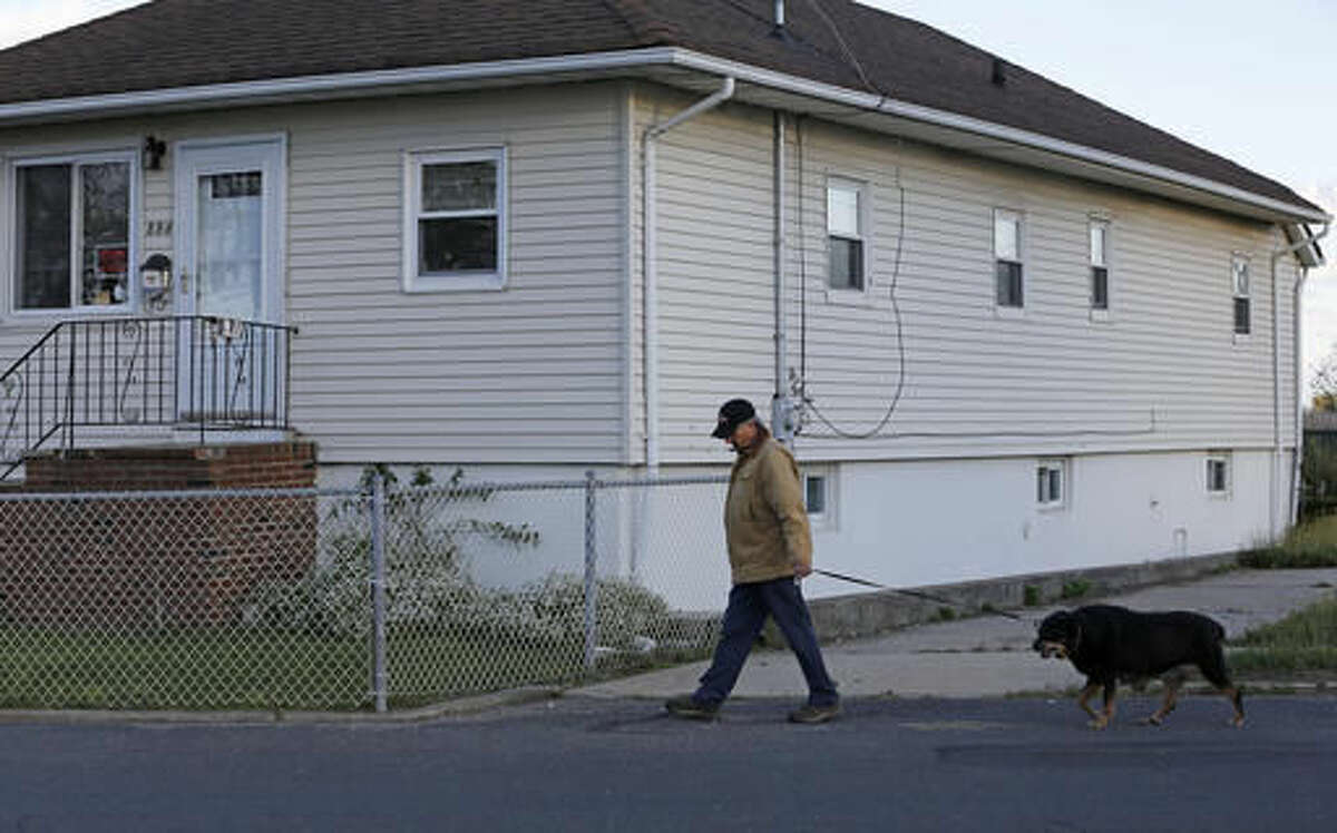 """In this Tuesday, Oct. 25, 2016 photo, resident Bobby Rosita walks his dog past his house, one of only a handful of occupied homes in the tiny neighborhood of Oakwood Beach in Staten Island, N.Y., four years after Superstorm Sandy's deadly storm surge flooded the area. Rosita said nearly all of the the homes near his are unoccupied after neighbors took advantage of a New York state buyout program designed to return the area to a wetland. Rosita, who was unhappy with the amount the government offered for his home, says he hasn't yet found a place to relocate, but will be out within a year when he plans to retire and move to Florida or """"someplace warmer."""" (AP Photo/Kathy Willens)"""
