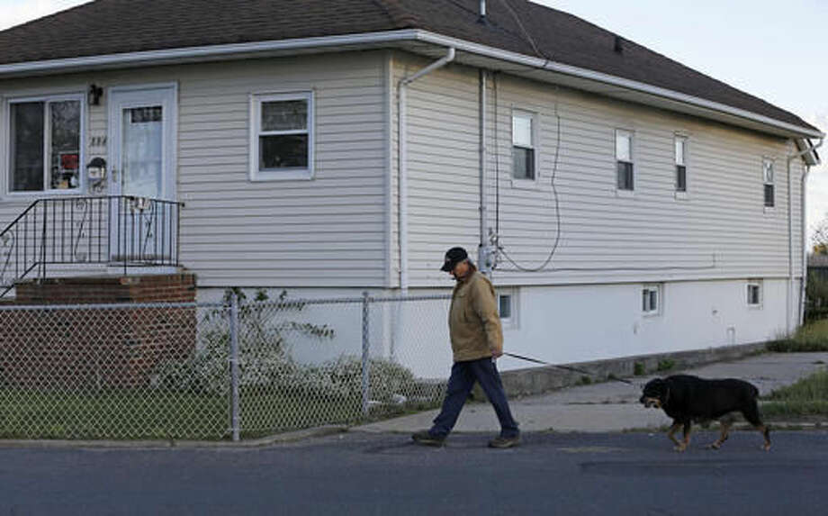 "In this Tuesday, Oct. 25, 2016 photo, resident Bobby Rosita walks his dog past his house, one of only a handful of occupied homes in the tiny neighborhood of Oakwood Beach in Staten Island, N.Y., four years after Superstorm Sandy's deadly storm surge flooded the area. Rosita said nearly all of the the homes near his are unoccupied after neighbors took advantage of a New York state buyout program designed to return the area to a wetland. Rosita, who was unhappy with the amount the government offered for his home, says he hasn't yet found a place to relocate, but will be out within a year when he plans to retire and move to Florida or ""someplace warmer."" (AP Photo/Kathy Willens)"