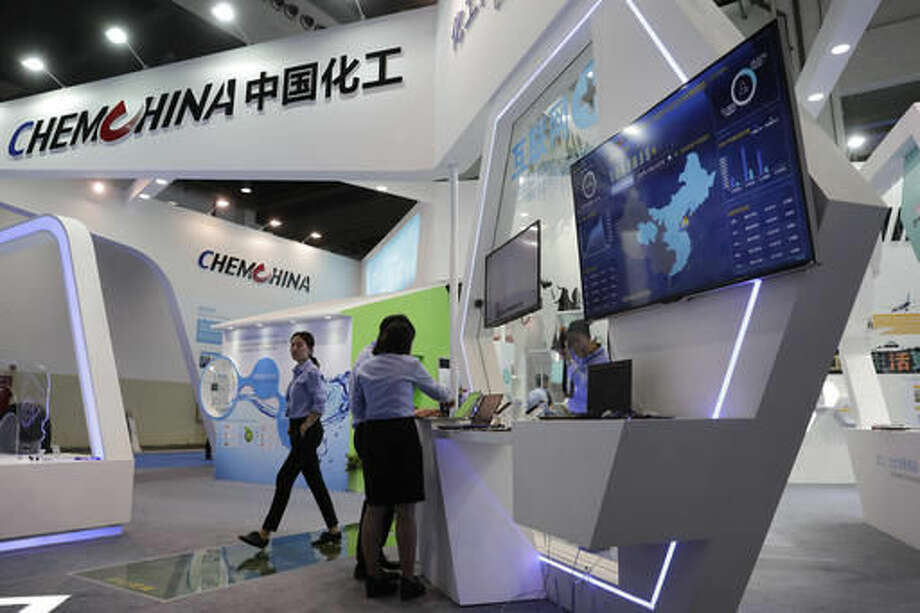 """In this Wednesday, Sept. 21, 2016 photo, workers set-up computers at the China National Chemical Corp., also known as ChemChina exhibition booth during the China International Chemical Industry Fair in Shanghai, China. Corporate China's global shopping binge rolled on this week with more multibillion dollar deals, but Beijing is starting to discover that there are limits to what its money can buy. Swiss chemical giant Syngenta said Tuesday, Oct. 25, 2016, that EU regulators examining its proposed $43 billion takeover by state-owned ChemChina have """"recently requested a large amount of additional information,"""" which will drag the approval process out into the first quarter of next year. (AP Photo/Andy Wong)"""