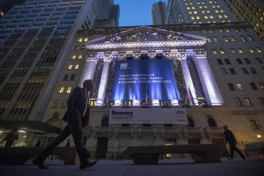 In this Tuesday, Oct. 25, 2016, photo, a pedestrian walks past the New York Stock Exchange, in lower Manhattan. U.S. stocks are edging higher early Thursday, Oct. 27, as health care companies rise following strong earnings for companies including drugmaker Bristol-Myers Squibb. Real estate companies continue to fall, and banks move higher as bond yields surge. Chipmaker Qualcomm said it will buy competitor NXP Semiconductors for $38 billion. (AP Photo/Mary Altaffer)