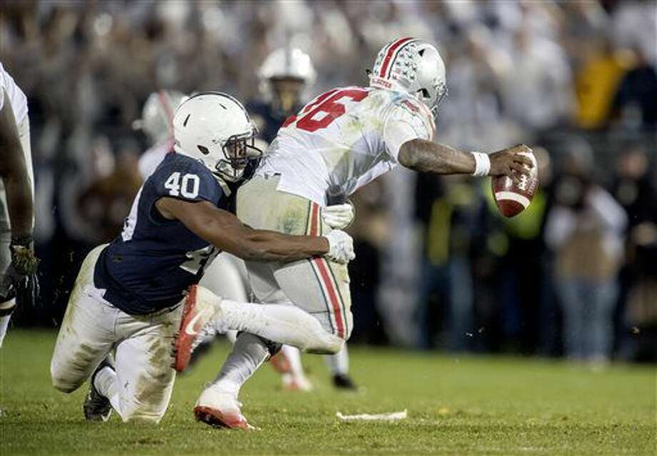 Penn State linebacker Jason Cabinda tackles Ohio State quarterback J.T. Barrett during an NCAA college football game Saturday, Oct. 22, 2016, in State College, Pa. Penn State won 24-21. (Abby Drey/Centre Daily Times via AP)