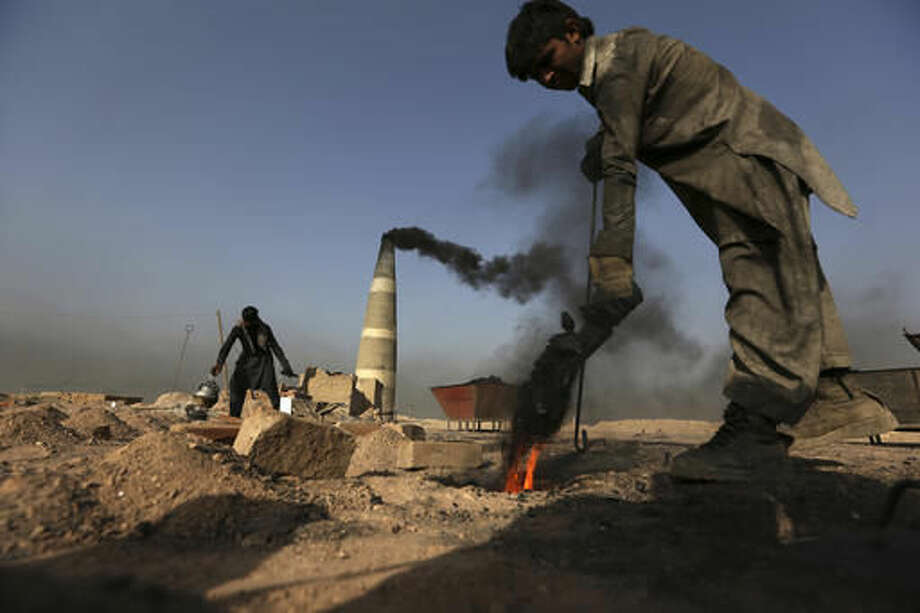 In this Oct. 4, 2016, photo, an Afghan laborer works at a brick factory in Deh Sabz, on the outskirts of Afghanistan's capital, Kabul. Each month, the Deh Sabz district's 350 kilns produce an average of 700,000 bricks, which in a six-month season totals 4.2 million each. That's 245 million bricks from just one district of Kabul, all made by indentured laborers, some of them children as young as 4 or 5 years old. (AP Photo/Rahmat Gul)