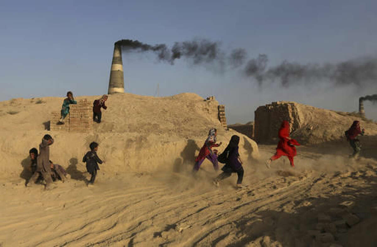 In this Oct. 3, 2016 photo, Afghan children, play at a brick factory in Deh Sabz, on the outskirts of Afghanistan's capital, Kabul. Each month, the Deh Sabz district's 350 kilns produce an average of 700,000 bricks, which in a six-month season totals 4.2 million each. That's 245 million bricks from just one district of Kabul, all made by indentured laborers, some of them children as young as 4 or 5 years old. (AP Photo/Rahmat Gul)