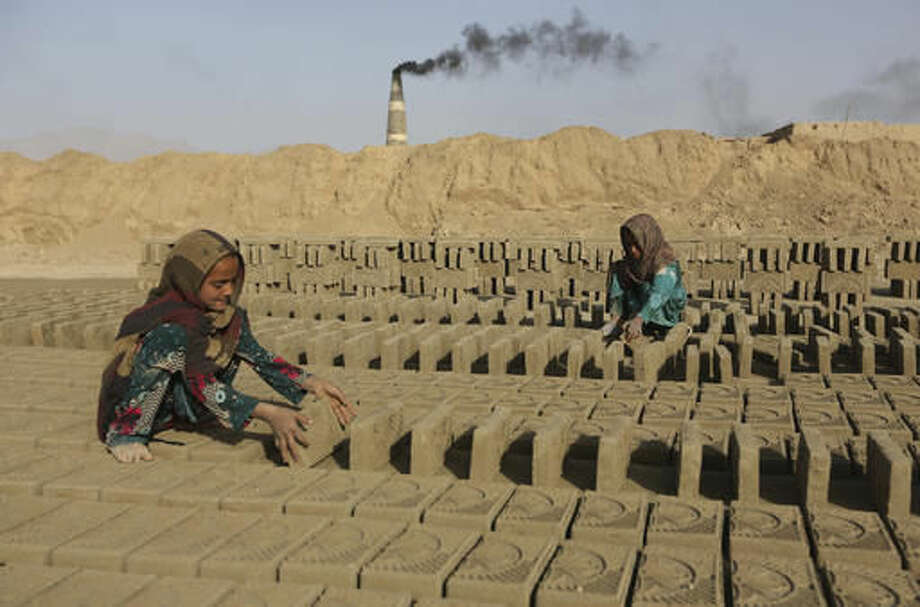 In this Oct. 3, 2016 photo, Afghan girls work in a brick factory in Deh Sabz, on the outskirts of Afghanistan's capital, Kabul. Each month, the Deh Sabz district's 350 kilns produce an average of 700,000 bricks, which in a six-month season totals 4.2 million each. That's 245 million bricks from just one district of Kabul, all made by indentured laborers, some of them children as young as 4 or 5 years old. (AP Photo/Rahmat Gul)