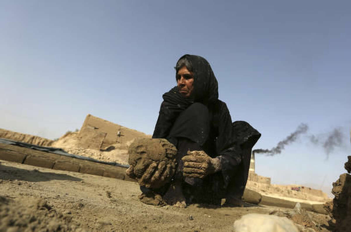 In this Oct. 3, 2016 photo, Alifa works in the late afternoon sun at a brick factory, in Deh Sabz, on the outskirts of Afghanistan's capital, Kabul. Alifa works to help her 70-year-old husband Gul Asgher and 28-year-old son Anwarullah pay off a 70,000 afghani (about $1,000) loan. She has seven other children and 12 grandchildren, she said. (AP Photo/Rahmat Gul)
