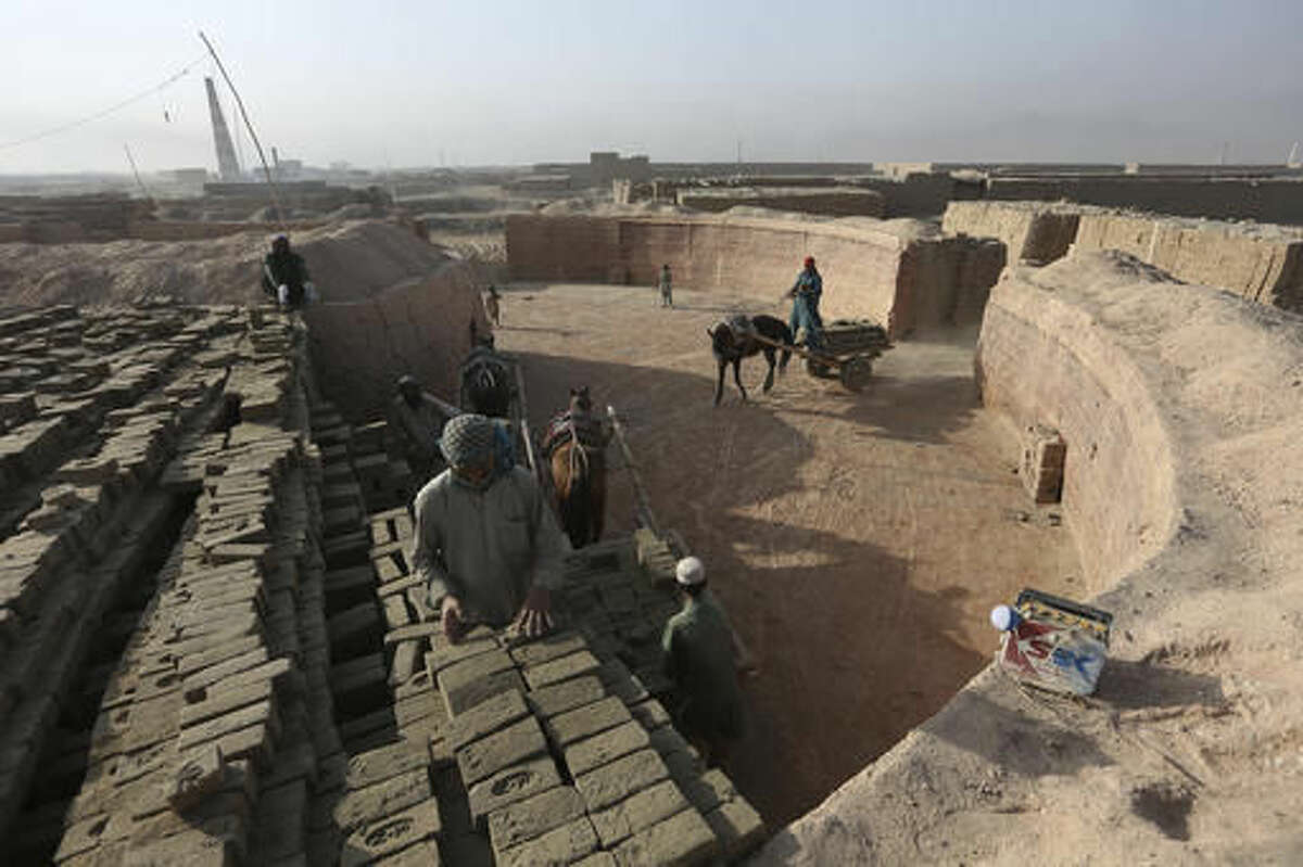 In this Tuesday, Oct. 4, 2016, photo, Afghan laborers work at a brick factory in Deh Sabz, on the outskirts of Afghanistan's capital, Kabul. Afghanistan is one of the poorest countries in the world, with a huge wealth divide: At the top are billionaires, at the very bottom are people like those working at the kiln in the Deh Sabz district. (AP Photo/Rahmat Gul)