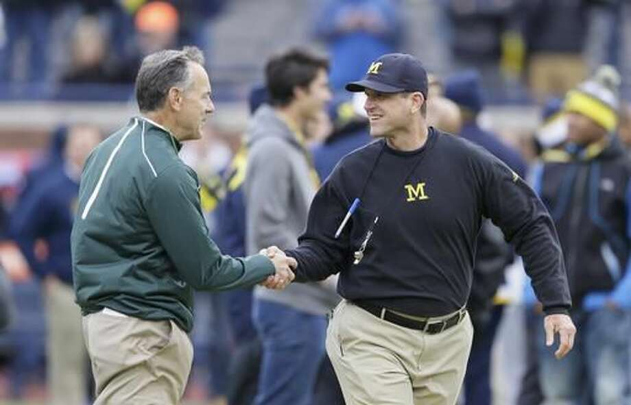 FILE - In this Oct. 17, 2015, file photo, Michigan State head coach Mark Dantonio, left, greets Michigan head coach Jim Harbaugh before an NCAA college football game in Ann Arbor, Mich. Dantonio believes Michigan State will upset No. 2 Michigan and he's not afraid to say it. In fact, Dantonio said in an interview with The Associated Press the Spartans' chances of winning Saturday are better than they were with 10 seconds left in last year's game at Michigan Stadium.(AP Photo/Carlos Osorio, FIle)