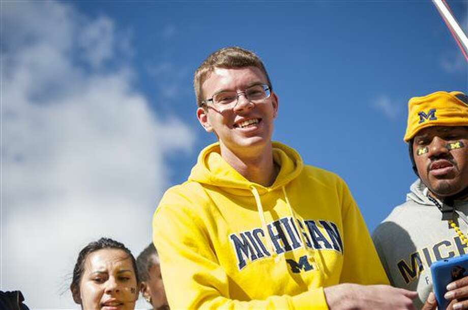 In this Oct. 22, 2016 photo, Chris Baldwin smiles before the start of the game between the University of Michigan verses the University of Illinois at Michigan Stadium, in Ann Arbor, Mich. Baldwin was made famous after being shown on television reacting to the last second win by Michigan State over Michigan in 2015. Michigan plays Michigan State Saturday, Oct. 29. (David Guralnick /Detroit News via AP)