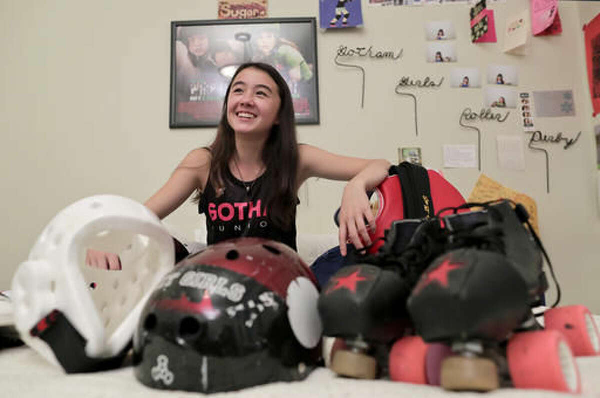 Alison Rogers poses for a photo with some of the jerseys and equipment she uses for the various sports she plays, including Tae Kwon Do and roller derby, at her home, Thursday, Oct. 27, 2016, in New York. After playing on her middle school football team last year as a backup cornerback and running back, the 13-year-old was prevented from rejoining her teammates this year when she declined to take an extra physical fitness performance test for girls required by New York State rules governing mixed gender competition. (AP Photo/Julie Jacobson)
