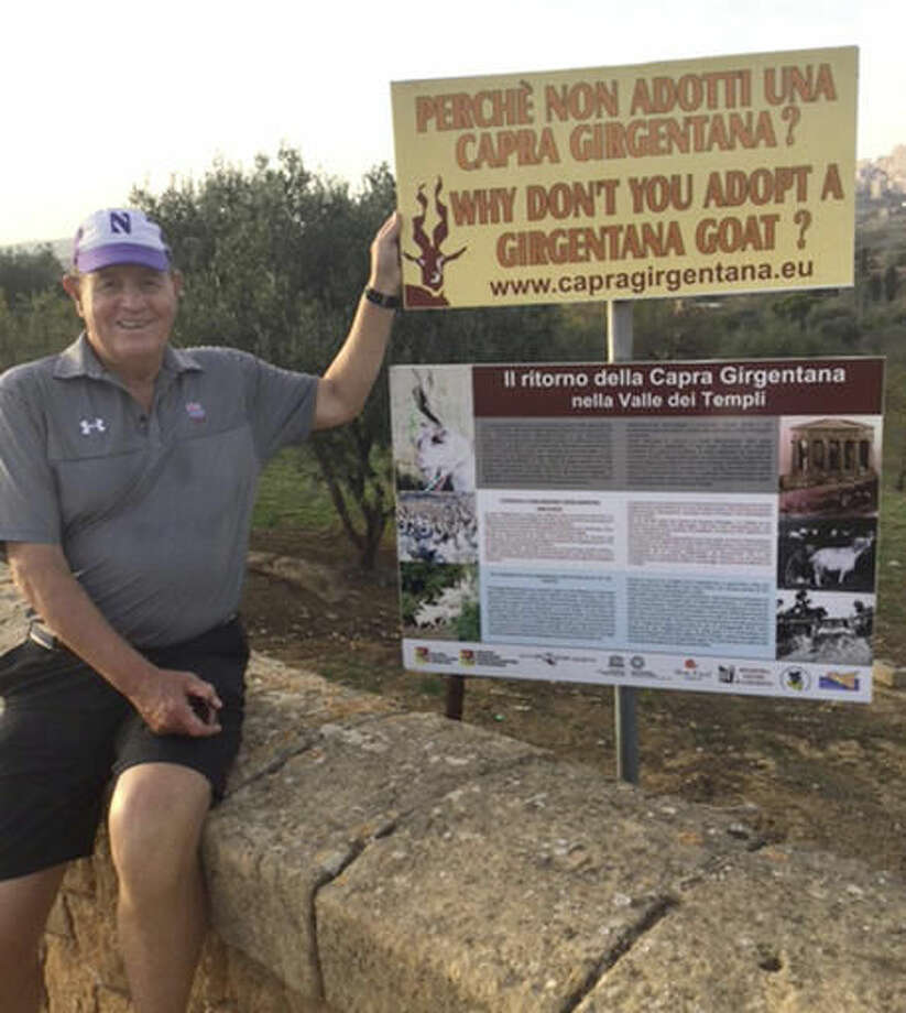 In this undated 2016 photo provided by the Logan family, Chuck Logan, the son of Olaf Logan, points to a sign offering goat for sale during a vacation in Sicily, Italy. Logan's late father Olaf Logan is said to be the Wrigley Field usher who was involved in the refusal to let the late Bill Sianis, owner of the Billy Goat Tavern in Chicago, attempt to get his goat into Wrigley Field during the Cubs 1945 World Series against the Detroit Tigers. The event led to the Sianis' curse that haut the Cubs in some fans' thoughts. (Courtesy of Chuck Logan via AP)