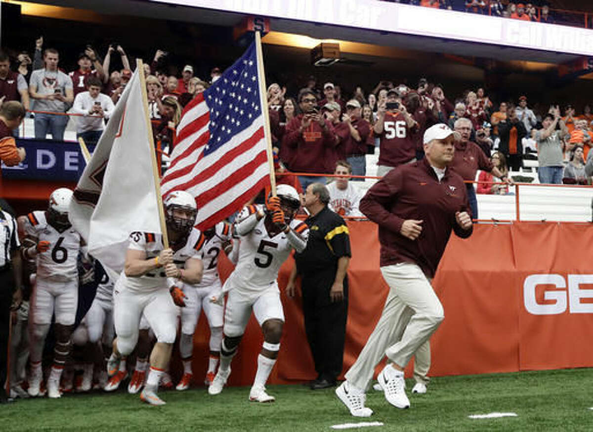 FILE - In this Saturday, Oct. 15, 2016, file photo, Virginia Tech head coach Justin Fuente leads his team to the field before an NCAA college football game against Syracuse in Syracuse, N.Y. Pitt and Virginia Tech meet on Thursday night with a chance to damage the other's ability to win the crowded ACC Coastal Division. (AP Photo/Mike Groll, File)