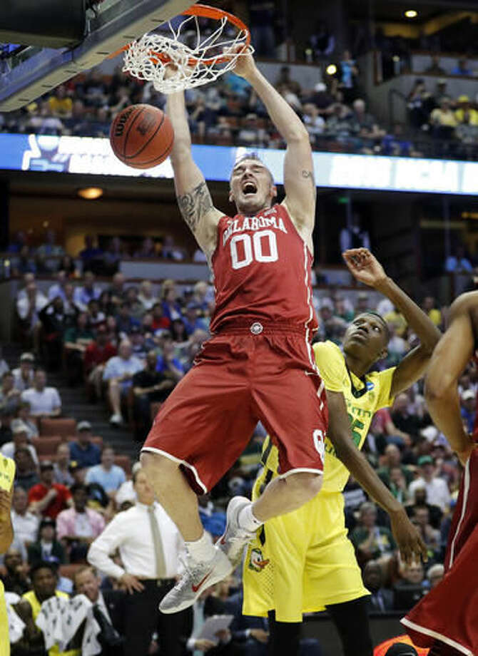 FILE - In this March 26, 2016, file photo, Oklahoma forward Ryan Spangler dunks over Oregon forward Chris Boucher during the first half of an NCAA college basketball game in the regional finals of the NCAA Tournament, Anaheim, Calif. Last season, Oklahoma reached the Final Four. This season, the coaches have picked the Sooners to finish sixth in the Big 12. (AP Photo/Gregory Bull, File)