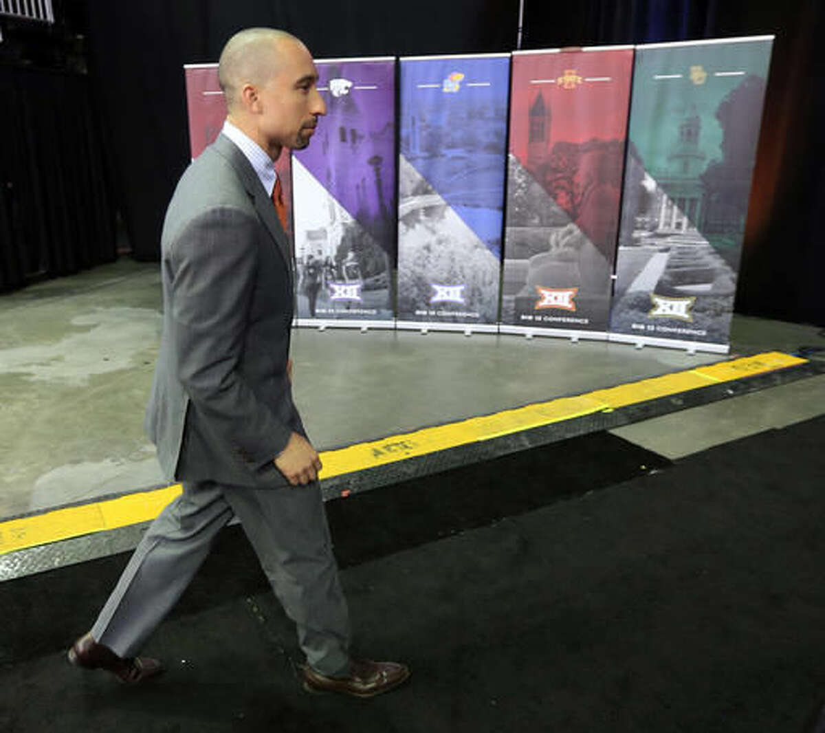 Texas coach Shaka Smart walks to a news conference during Big 12 NCAA college basketball media day in Kansas City, Mo., Tuesday, Oct. 25, 2016. (AP Photo/Orlin Wagner)