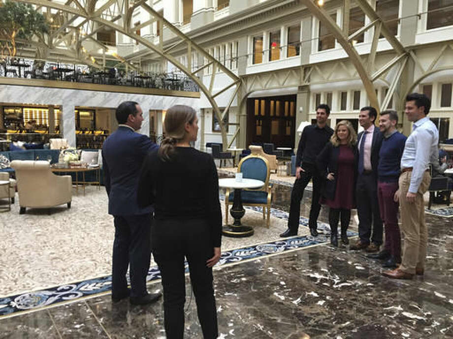 In this photo taken Oct. 25, 2016, Donald Trump Jr. poses with visitors in the lobby of the Trump International Hotel in Washington, D.C. Trump, who repeatedly stopped him to shake hands as he walked through the hotel. The son of the presidential candidate Donald Trump says that despite reports that the hotel brand is flailing and slashing rates, the new hotel is busy and he expects to welcome both Democrats and Republicans as guests. His father, the presidential candidate, was scheduled to appear at the hotel Wednesday, Oct. 26, 2016, for a ribbon cutting. (AP Photo/Beth J. Harpaz)