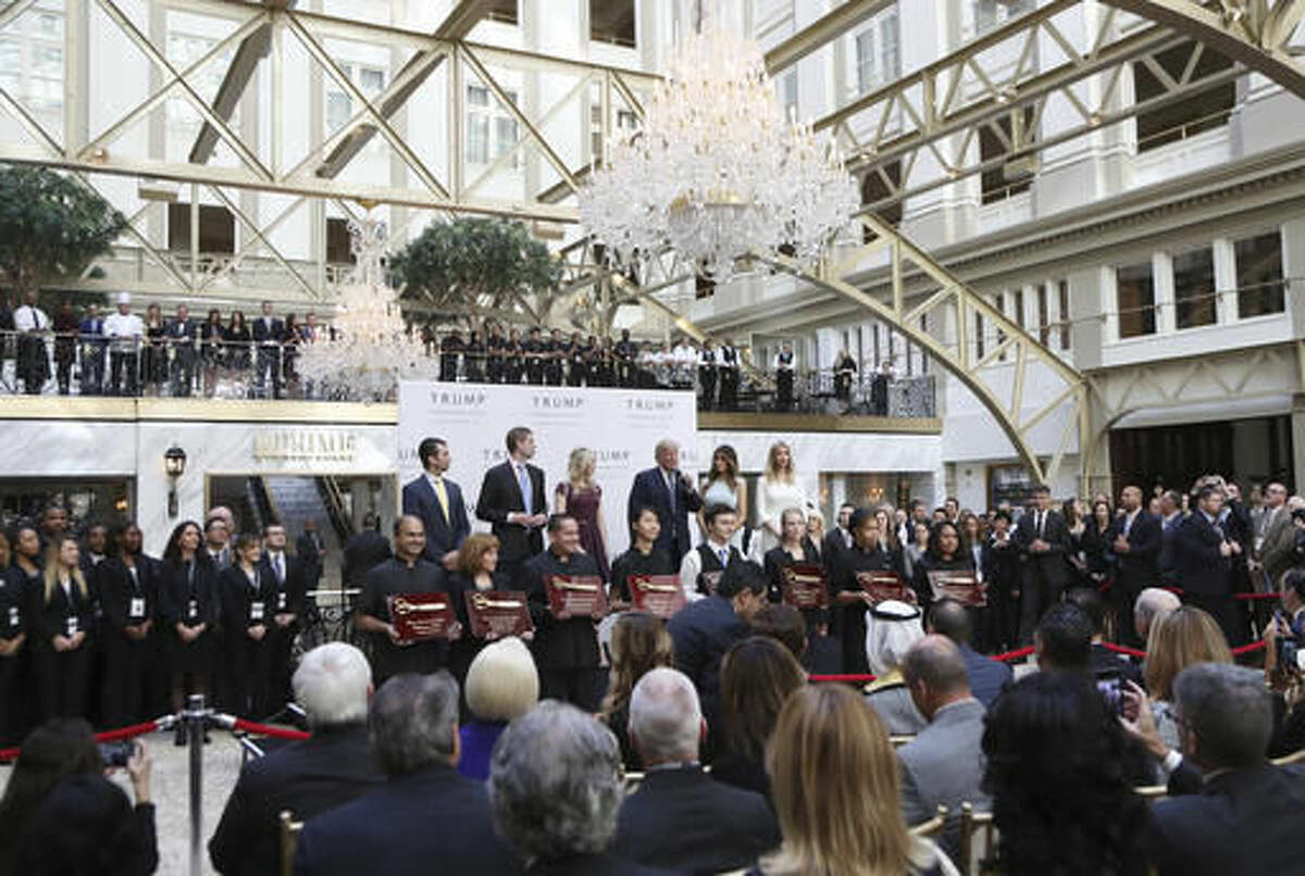Republican presidential candidate Donald Trump, together with his family, from left, Donald Trump Jr., Eric Trump, Trump, Melania Trump, Tiffany Trump and Ivanka Trump, speaks in the hotel lobby, during the grand opening of Trump International Hotel in Washington, Wednesday, Oct. 26, 2016. Donald Trump and his children hosted an official ribbon cutting ceremony and press conference to celebrate the grand opening of his new hotel. (AP Photo/Manuel Balce Ceneta