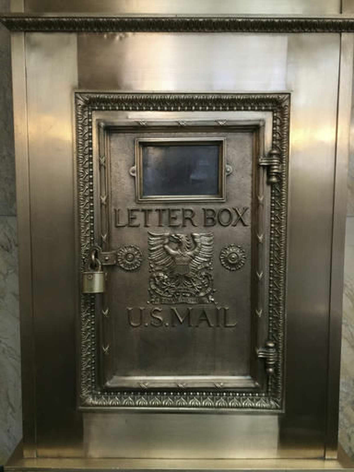 In this photo taken Oct. 25, 2016, an old mail chute in a hallway at the Trump International Hotel in Washington. The hotel is located in a historic 1899 building called the Old Post Office that was once part of the postal system. The Trump hotel organization made a deal with federal agencies to renovate the building and operate it as a hotel. While many elements like this mail chute have been preserved, there's also been some criticism that the renovation covers up some of the original decor, such as carpeting over marble flooring and drapes over walls, while adding too much glitz, like gold leaf. Donald Trump was scheduled to appear at the hotel Wednesday, Oct. 26, 2016, for a ribbon cutting. (AP Photo/Beth J. Harpaz)
