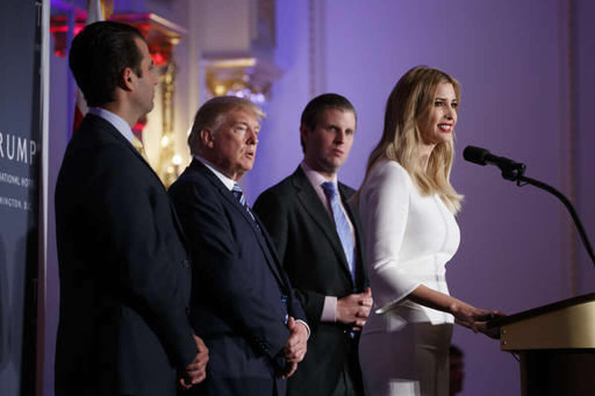 Republican presidential candidate Donald Trump, flanked by his sons, Donald Trump Jr., left, and Eric Trump, listens on as his daughter Ivanka Trump speaks during the grand opening of the Trump International Hotel- Old Post Office, Wednesday, Oct. 26, 2016, in Washington. (AP Photo/ Evan Vucci)