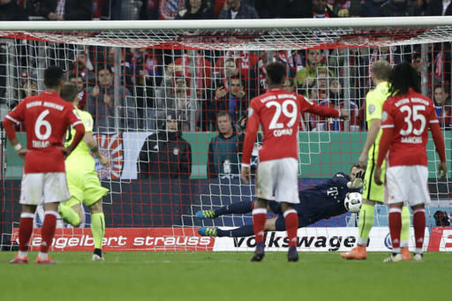 Bayern goalkeeper Manuel Neuer saves a penalty shot by Augsburg's Daniel Baier during the German Soccer Cup match between FC Bayern Munich and FC Augsburg at Allianz Arena stadium in Munich, Germany, Wednesday, Oct. 26, 2016. (AP Photo/Matthias Schrader)