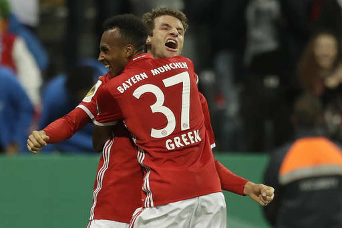 Bayern's Julian Green, back to camera, celebrates with teammate Thomas Mueller after scoring his side's second goal during the German Soccer Cup match between FC Bayern Munich and FC Augsburg at Allianz Arena stadium in Munich, Germany, Wednesday, Oct. 26, 2016. (AP Photo/Matthias Schrader)
