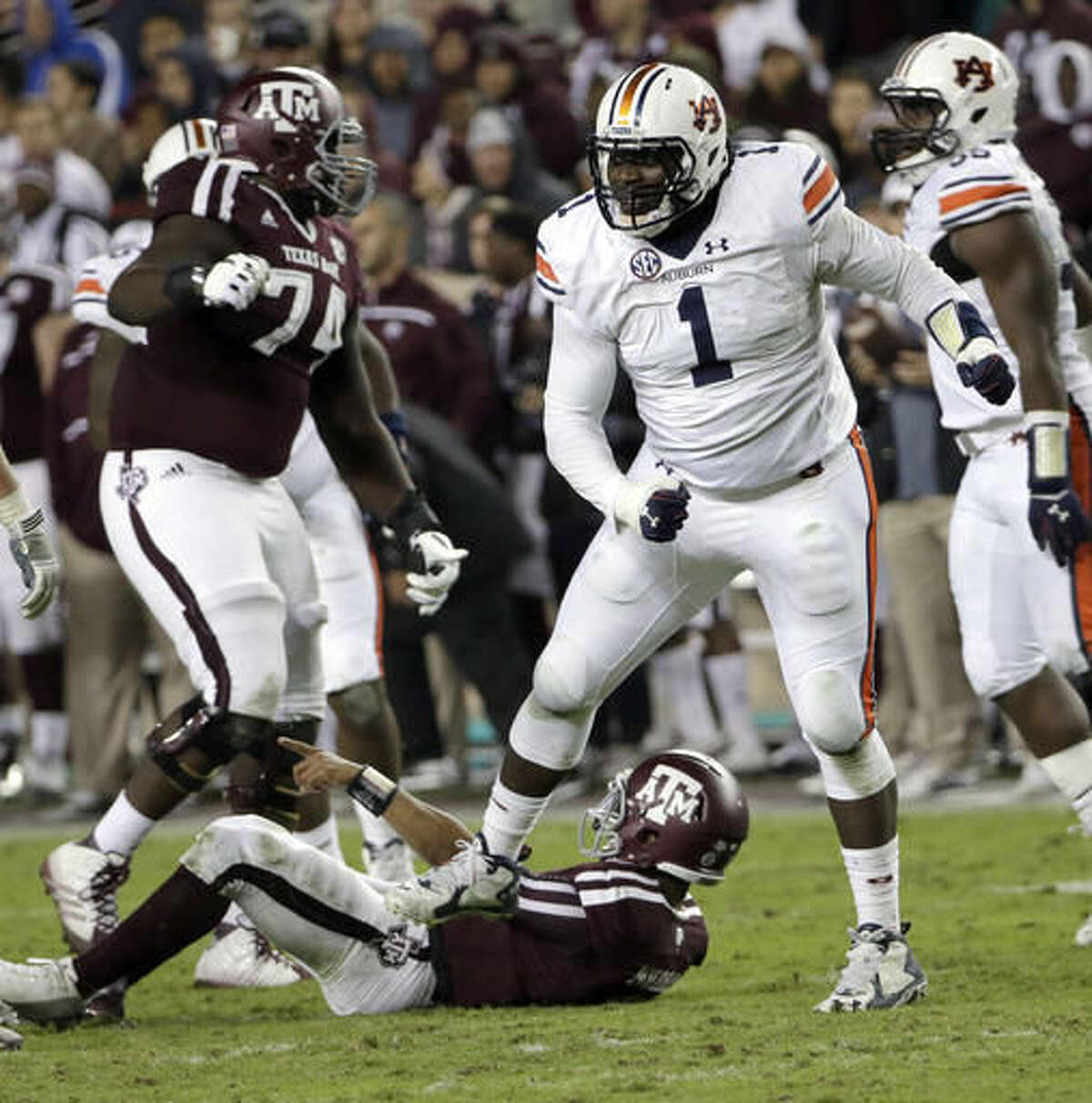 FILE - In this Nov. 7, 2015, file photo, Auburn defensive tackle Montravius Adams (1) celebrates after sacking Texas A&M quarterback Kyler Murray, bottom, during the second quarter of an NCAA college football game, in College Station, Texas. Auburn defensive linemen Montravius Adams and his teammate Carl Lawson have been at the forefront of the Tigers' resurgence (AP Photo/David J. Phillip, File)