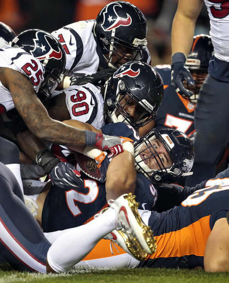 Denver Broncos running back C.J. Anderson, center, falls in for a touchdown as Houston Texans defensive end Jadeveon Clowney (90), nose tackle Vince Wilfork (75) and cornerback Kareem Jackson (25) defend during the second half of an NFL football game, Monday, Oct. 24, 2016, in Denver. (AP Photo/Joe Mahoney)