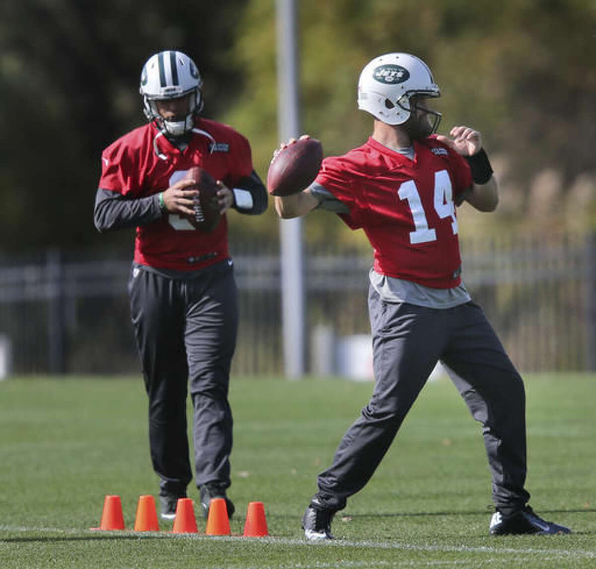 New York Jets quarterback Ryan Fitzpatrick, right, throws while Bryce Petty looks on during a NFL football practice in Florham Park, N.J., Wednesday, Oct. 26, 2016. (AP Photo/Seth Wenig)