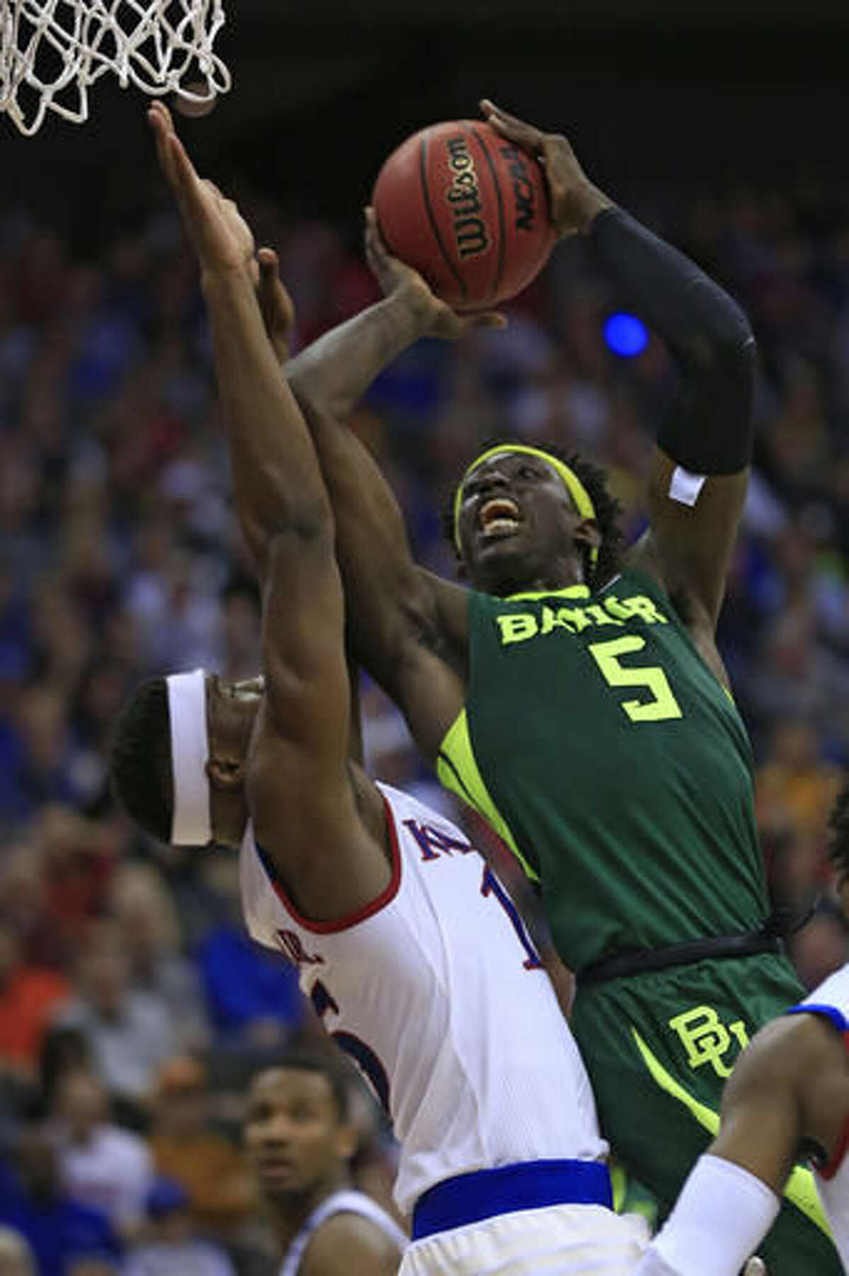 FILE - In this Friday, March 11, 2016, file photo, Baylor forward Johnathan Motley (5) goes to the basket as Kansas forward Carlton Bragg Jr. (15) defends during the second half of an NCAA college basketball game in the semifinals of the Big 12 conference tournament in Kansas City, Mo. Baylor has become an NCAA Tournament regular under coach Scott Drew. (AP Photo/Orlin Wagner, File)