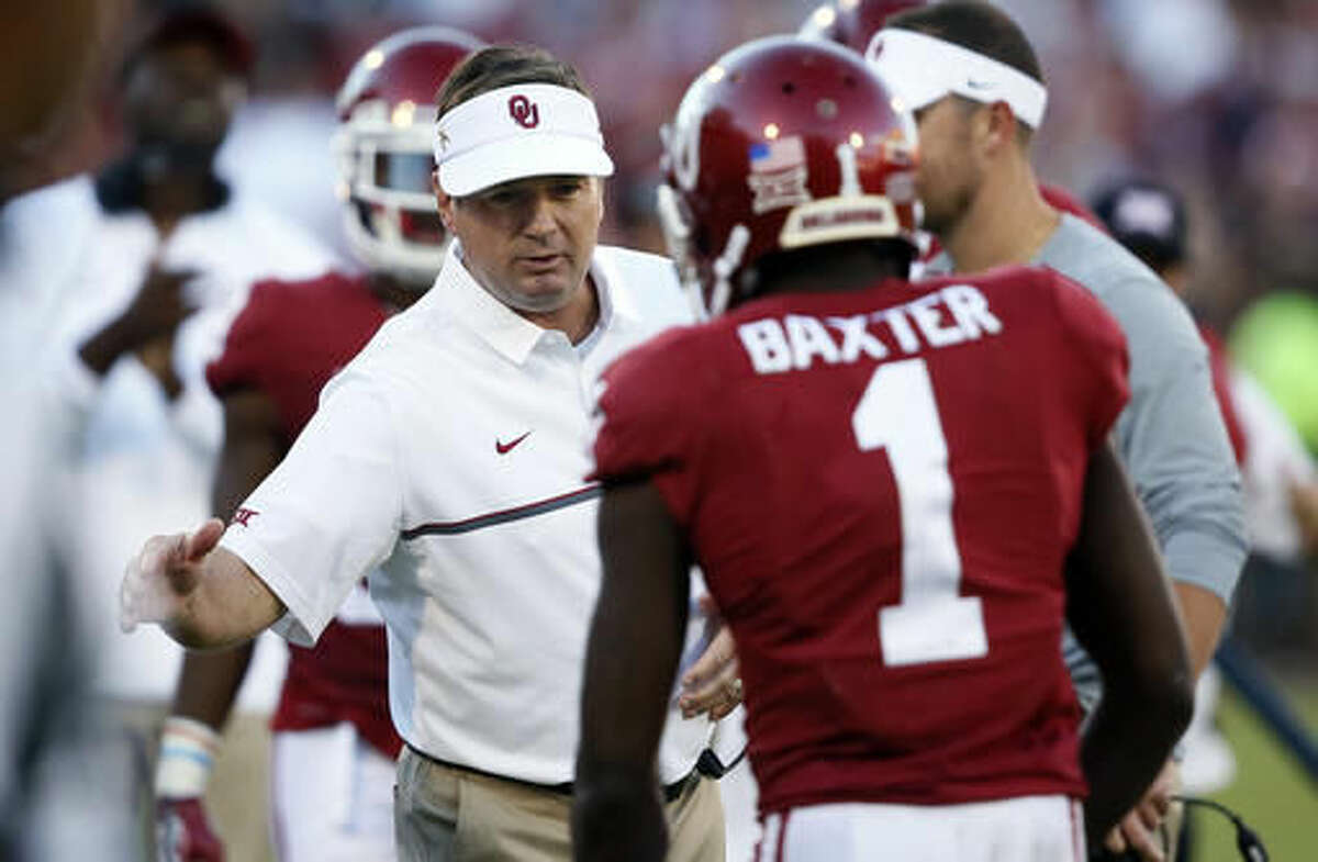 FILE - In this Sept. 1o, 2016, file photo, Oklahoma head coach Bob Stoops, left, greets wide receiver Jarvis Baxter (1) following a touchdown against Louisiana Monroe during an NCAA college football game in Norman, Okla. With Baylor and West Virginia still undefeated before the first CFP rankings, there could still be playoff hopes for the Big 12. And could there be a potential path for two-loss Oklahoma to get back in contention for a return to the playoff?(AP Photo/Sue Ogrocki, File)