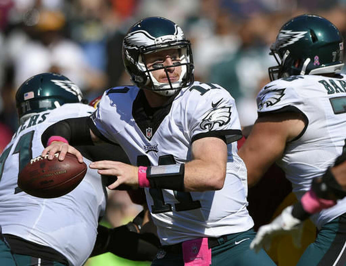 FILE - In this Sunday, Oct. 16, 2016, file photo, Philadelphia Eagles quarterback Carson Wentz throws to a receiver in the first half of an NFL football game against the Washington Redskins in Landover, Md. Dallas' Dak Prescott and Philadelphia's Carson Wentz enjoyed a week together at the Senior Bowl, likely not considering they might soon be rival rookie quarterbacks starting a key NFC East game. Through distinctly different circumstances, they will meet Sunday night. (AP Photo/Nick Wass, File)