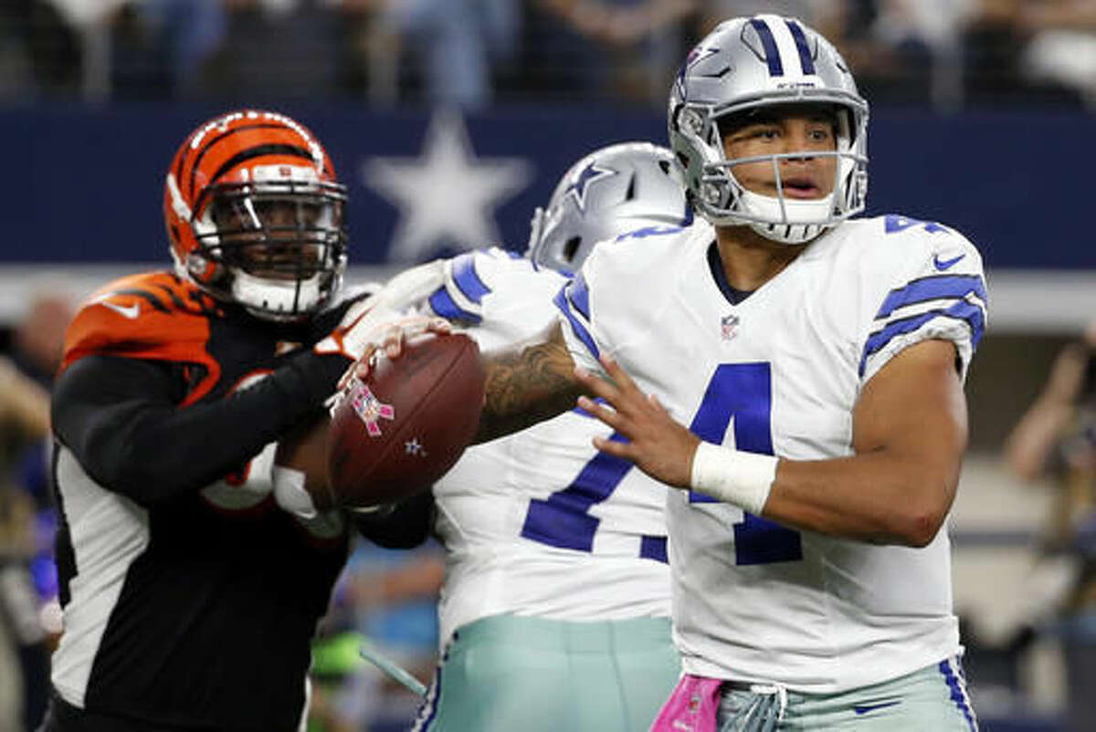 FILE - In this Sunday, Oct. 9, 2016, file photo, Dallas Cowboys quarterback Dak Prescott (4) prepares to throw a pass under pressure from Cincinnati Bengals defensive end Michael Johnson, left, in the second half of an NFL football game in Arlington, Texas. Dallas' Dak Prescott and Philadelphia's Carson Wentz enjoyed a week together at the Senior Bowl, likely not considering they might soon be rival rookie quarterbacks starting a key NFC East game. Through distinctly different circumstances, they will meet Sunday night. (AP Photo/Michael Ainsworth, File)