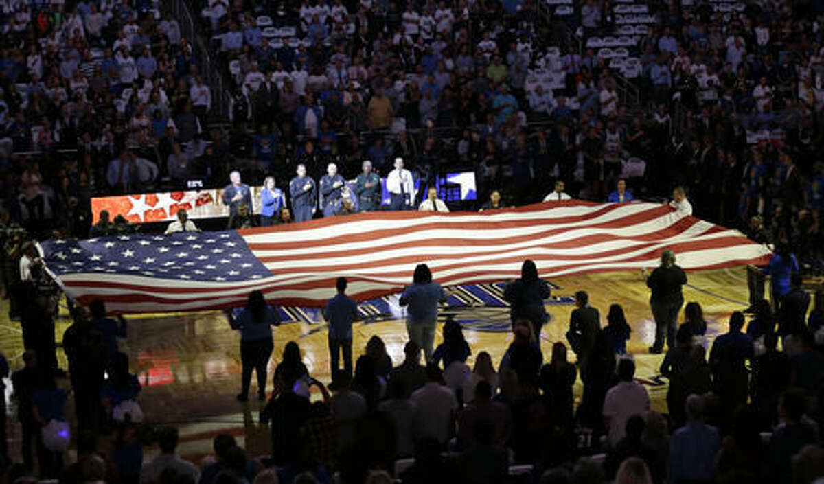 First responders hold a flag on the court as the national anthem is played during a tribute to the victims of the Pulse nightclub shooting prior to an NBA basketball game between the Orlando Magic and the Miami Heat, Wednesday, Oct. 26, 2016, in Orlando, Fla. (AP Photo/John Raoux)