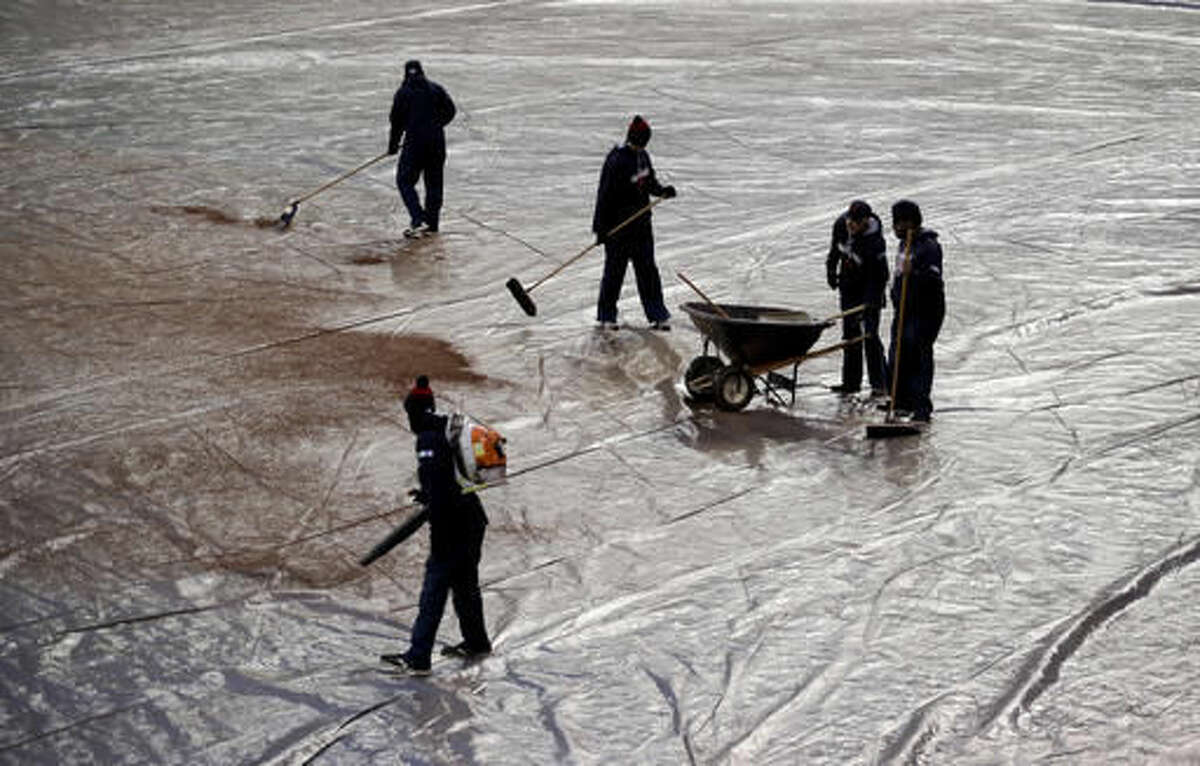 Members of the grounds crew clean off the tarp before Game 2 of the Major League Baseball World Series between the Cleveland Indians and the Chicago Cubs Wednesday, Oct. 26, 2016, in Cleveland. (AP Photo/Charlie Riedel)