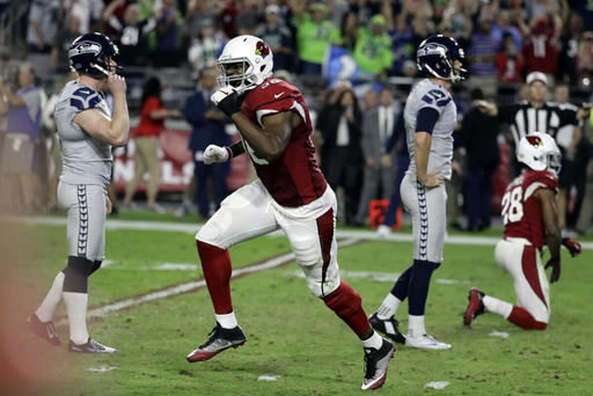 Arizona Cardinals linebacker Kareem Martin, center, reacts to Seattle Seahawks kicker Stephen Hauschka's, left, missed game-winning field goal attempt during overtime an NFL football game against the Arizona Cardinals, Sunday, Oct. 23, 2016, in Glendale, Ariz. The game ended in overtime in a 6-6 tie. (AP Photo/Rick Scuteri)