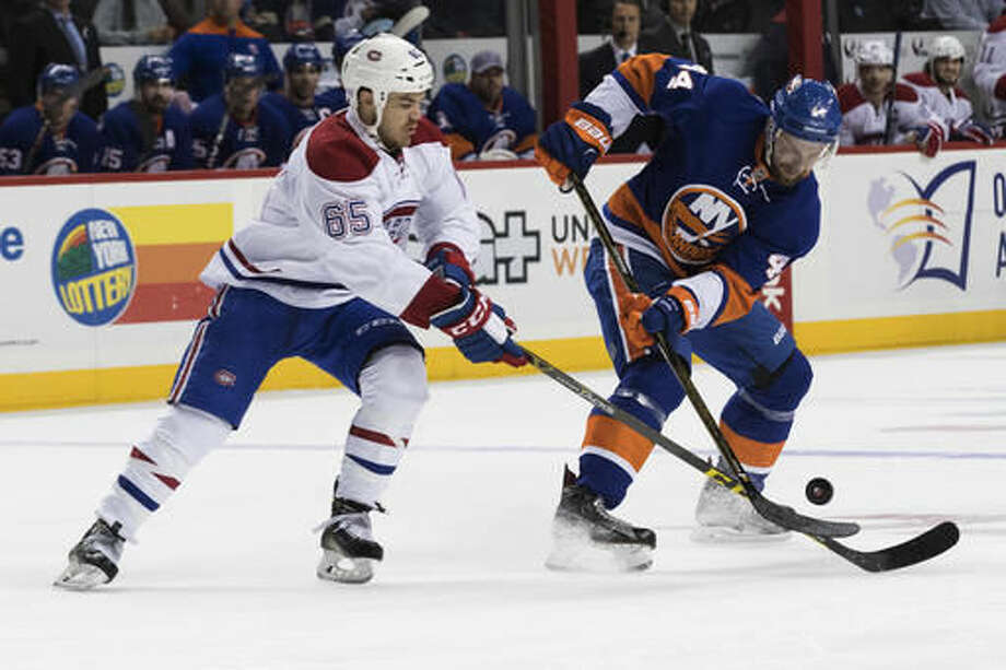 Montreal Canadiens center Andrew Shaw (65) fights for the puck against New York Islanders defenseman Calvin de Haan (44) during the first period of an NHL hockey game Wednesday, Oct. 26, 2016 in New York. (AP Photo/Mary Altaffer)