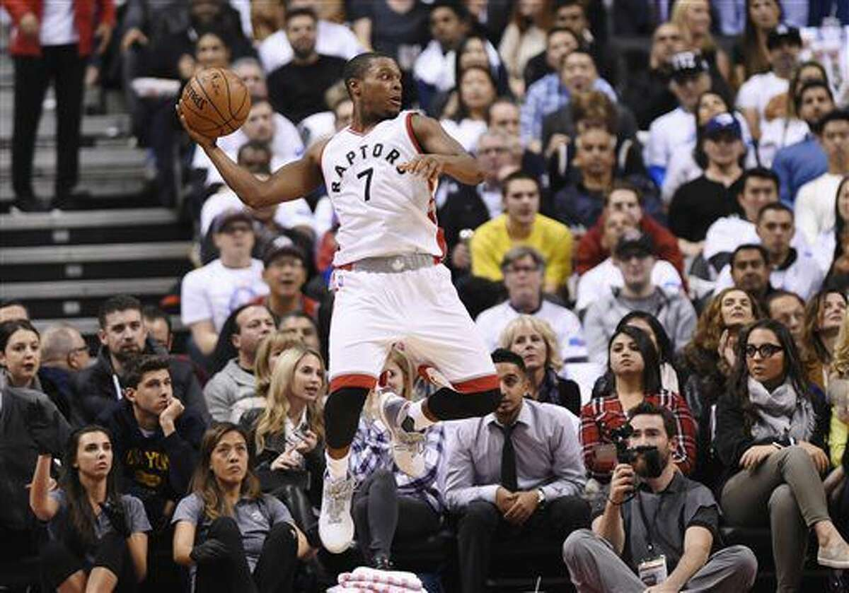 Toronto Raptors guard Kyle Lowry (7) keeps the ball from going out of bounds against the Detroit Pistons during the first half of an NBA basketball game in Toronto on Wednesday, Oct. 26, 2016. (Nathan Denette/The Canadian Press via AP)