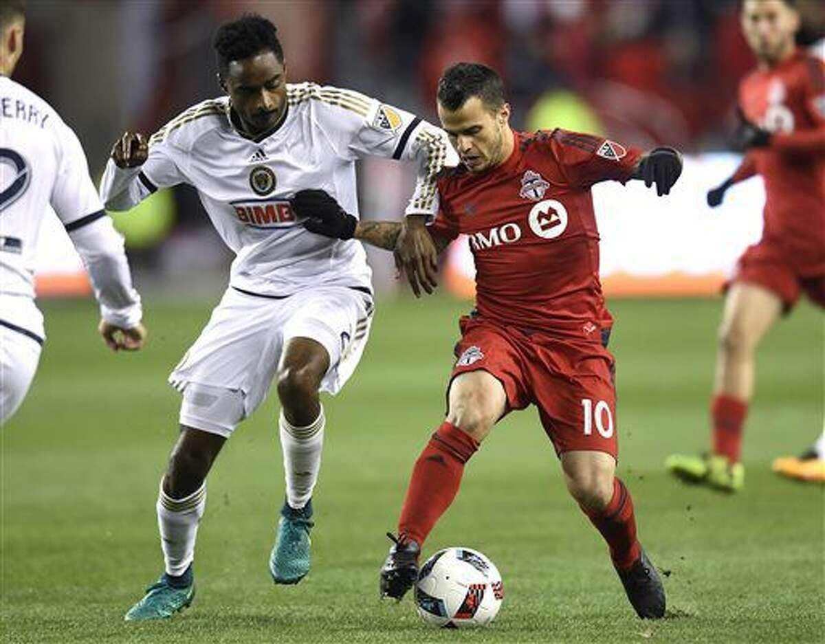 Toronto FC's Sebastian Giovinco, right, battles with Philadelphia Union's Warren Creavalle during the first half of an MLS soccer playoff match in Toronto, Wednesday, Oct. 26, 2016. (Frank Gunn/The Canadian Press via AP)