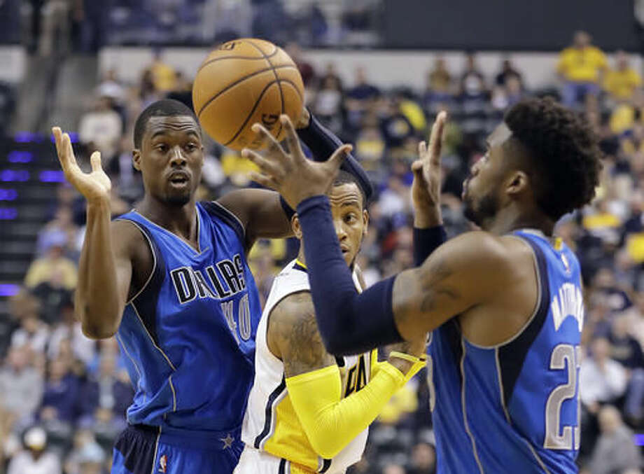 Dallas Mavericks' Harrison Barnes (40) makes a pass to Wesley Matthews (23) as Indiana Pacers' Monta Ellis (11) watches during the first half of an NBA basketball game Wednesday, Oct. 26, 2016, in Indianapolis. (AP Photo/Darron Cummings)