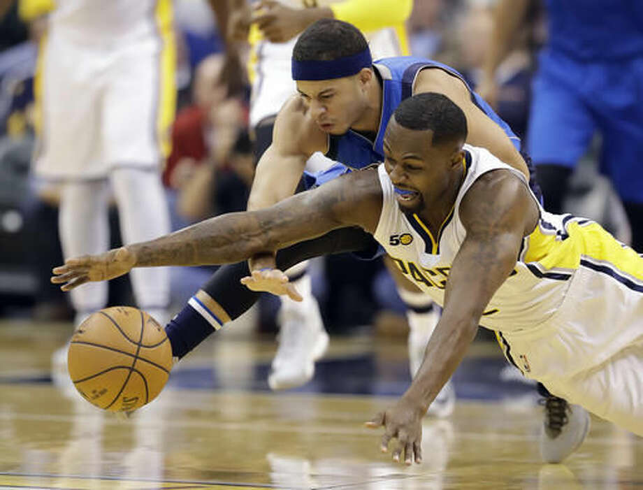 Indiana Pacers' Rodney Stuckey and Dallas Mavericks' Seth Curry dive for a loose ball during the first half of an NBA basketball game Wednesday, Oct. 26, 2016, in Indianapolis. (AP Photo/Darron Cummings)